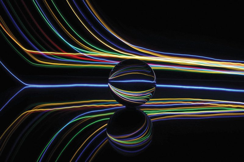 Colourful lines of light against a black background skirt around a marble