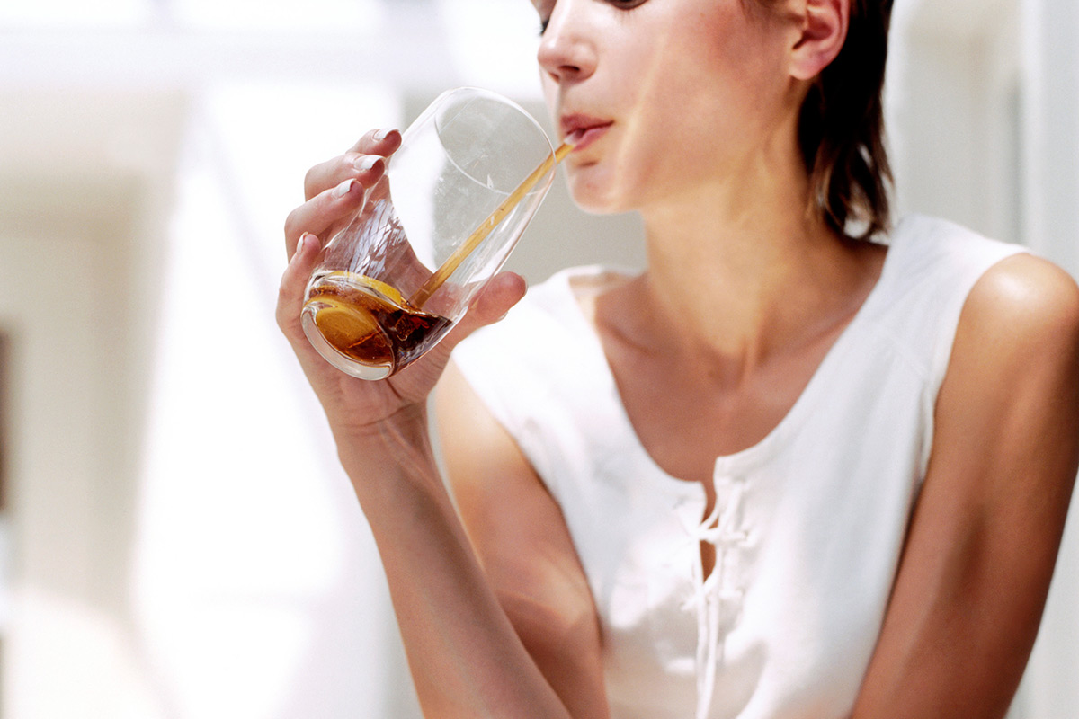 A woman drinking a fizzy drink