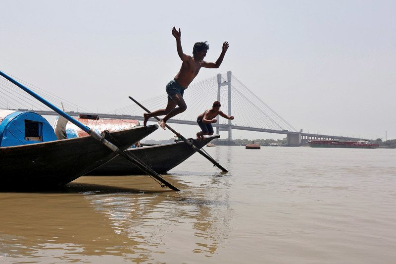 Two boys jumping from a boat into the Ganges river