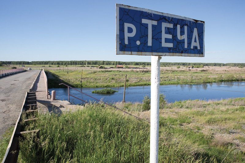 Road sign with Cyrillic script with river and grassland beyond