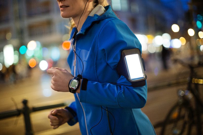 Person with smartphone strapped to their arm in a city