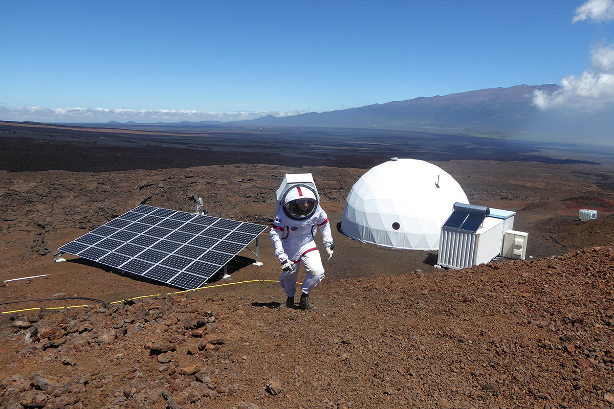 Sheyna Gifford in spacesuit walking up a slope