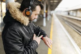 Man wearing smartwatch at train station