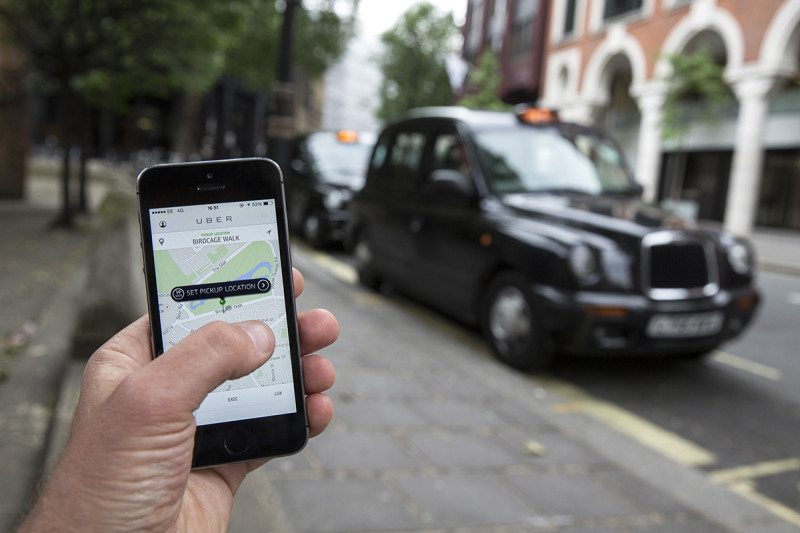 In the background, a regular black cab is parked beside the pavement of a suburban street, in the foreground a hand is holding a smartphone running the Uber app