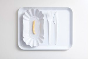 A single French fry on a paper plate with plastic cutlery beside it