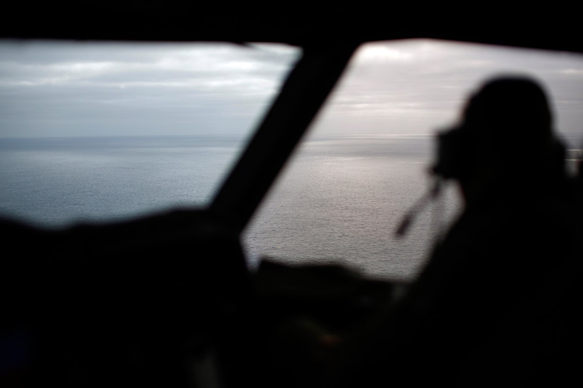 Cockpit shot of pilot looking out at ocean