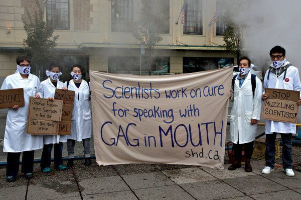 "People in white lab coats hold banner reading ""Scientists work on cure for speaking with gag in mouth"""