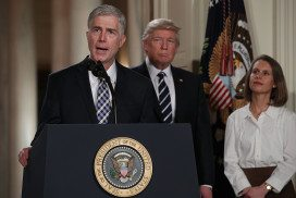 Neil Gorsuch at podium with Trump in background