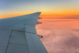 Aircraft's wing with rosy horizon beyond