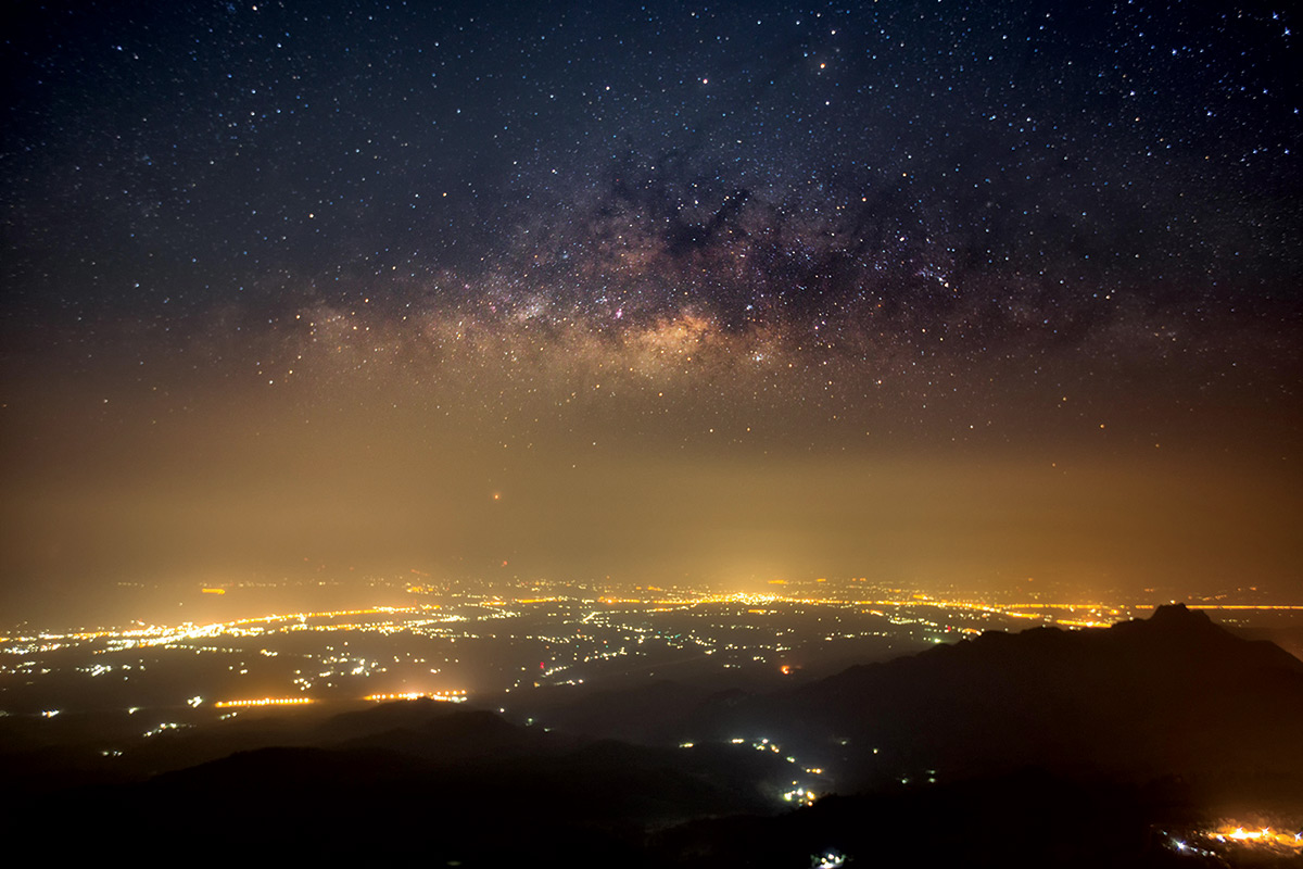 Plain full of city lights with Milky Way above