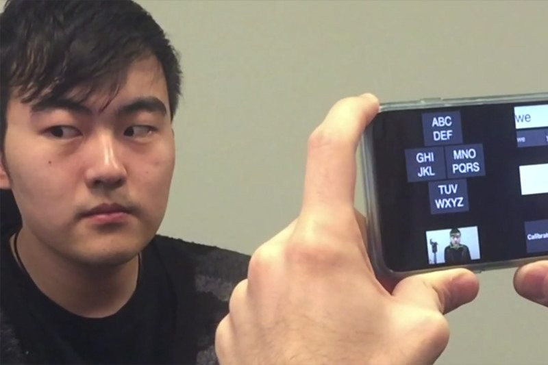 A smartphone held up in front of a person gazin to the right, showing the GazeSpeak app on the phone screen
