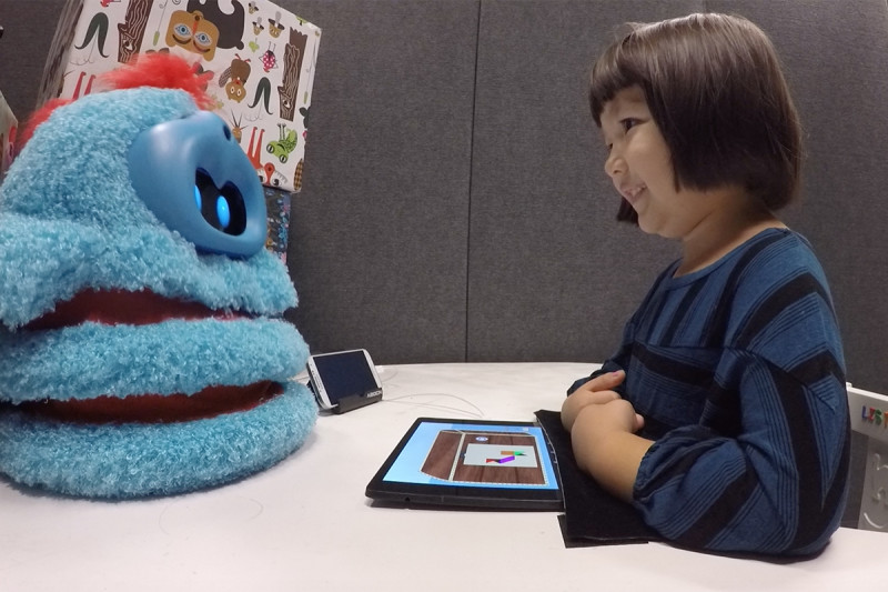 A similing child sits opposite a fluffy blue robot companion on a desk