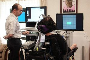 A person in a wheelchair looks towards a screen with a grid on it while a researcher looks on