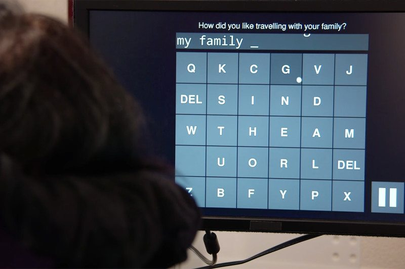 A close-up of a screen with a grid of letters with a cursor hovering over one, part way through typing a sentence