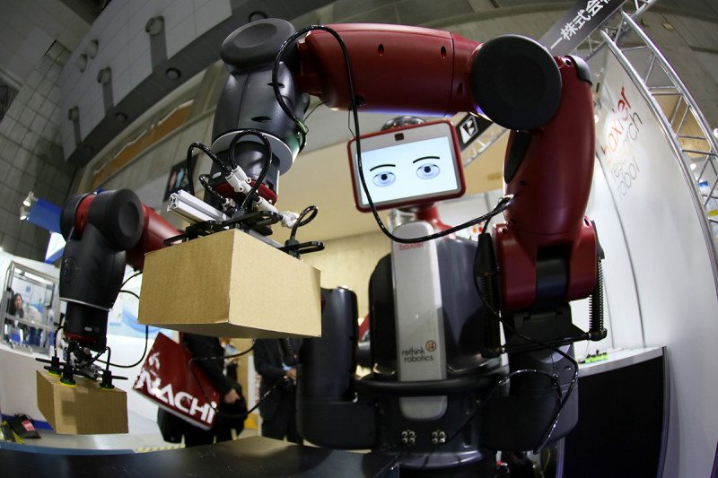 A Baxter robot moving a box with its arm