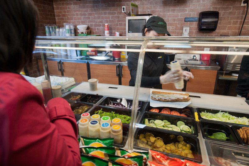 A person stands in front of the counter in a Subway restaurant as the server assembles a sandwich