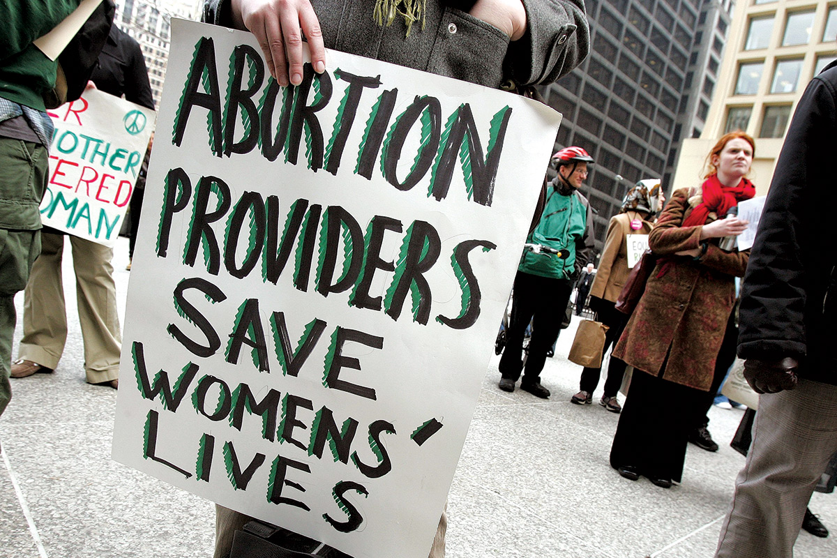 person holding a banner saying'abortion providers save womens' lives'