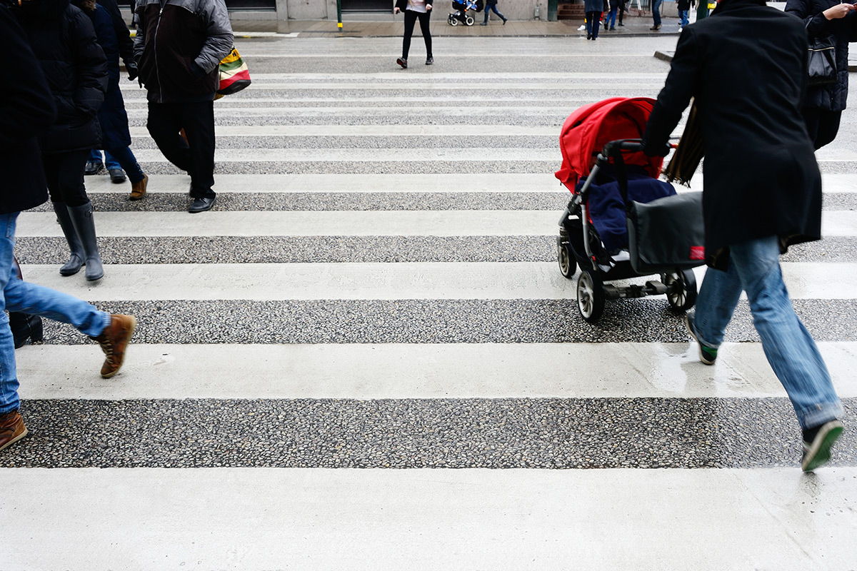 A pram being pushed across a zebra crossing
