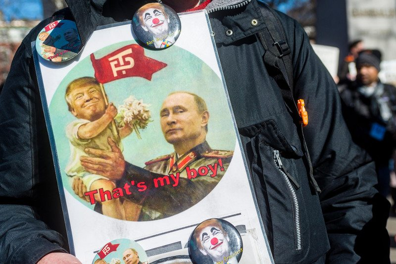 "A poster with Donals Trump as a child in Vladimir Putin's arms with the text ""That's my boy!"""