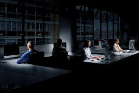 People at computers sitting in a darkened office