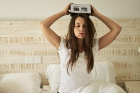 Tired woman holding alarm clock on head
