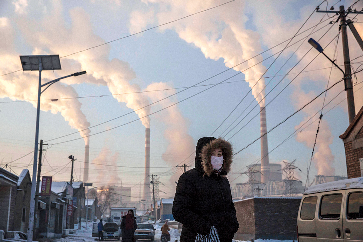 Woman in face mask walks in front of chimneystacks