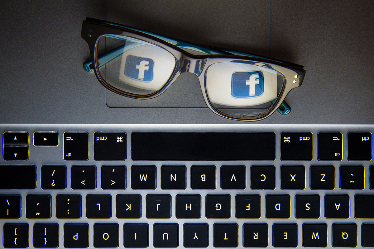 A pair of glasses next to a computer keyboard reflecting the Facebook logo