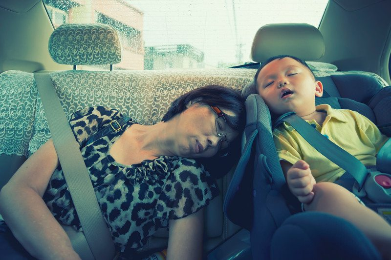 Two People Asleep In The Back Of A Car Possibly Dreaming