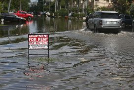 Sign advertising property to rent on flooded street