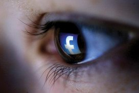 Close-up of an eye with the Facebook logo reflected in it