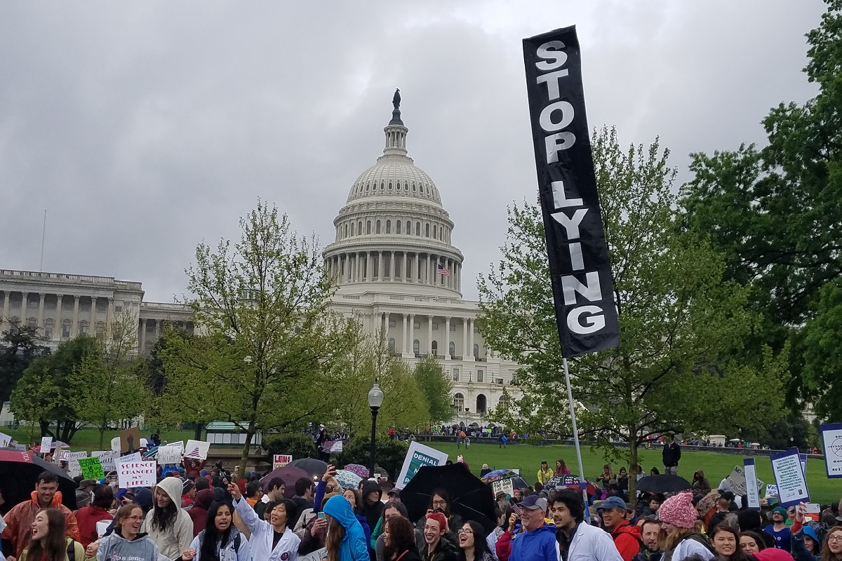"Marchers in front of the Capitol Building in Washington, DC, with a sign saying ""Stop Lying"""
