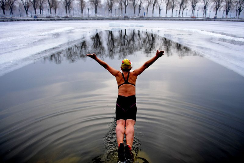 A swimmer diving into an icy lake