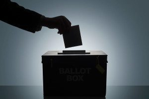 Hand putting voting paper in ballot box