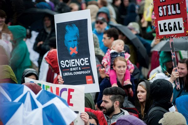 """Person holds placard reading """"Science is not a liberal conspiracy"""""""
