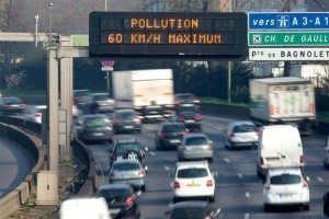traffic on a busy road with pollution warning  sign