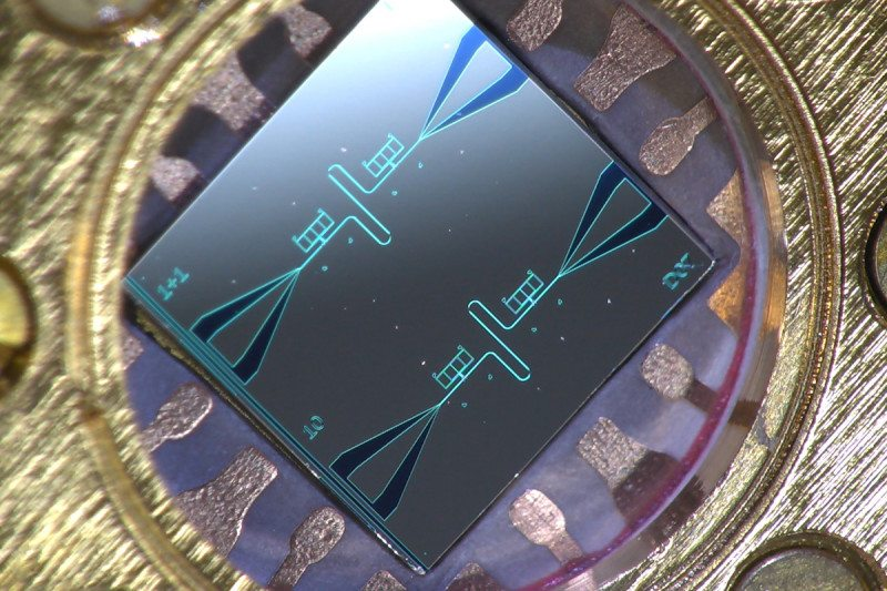 Centimeter-sized silicon chip, which has two parallel superconducting oscillators and the quantum-circuit refrigerators connected to them