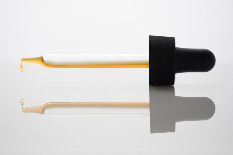 A pipette dripping a gold coloured liquid