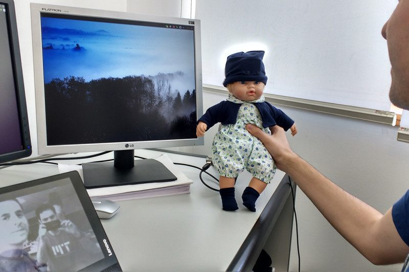 Man holds doll next to computer screen