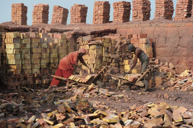 Slave labourers piling red bricks into trolleys