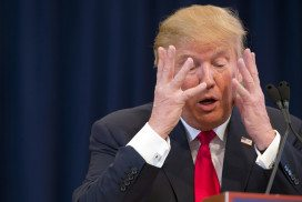 Donald Trump with his hands up covering his face