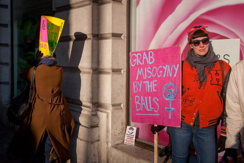 "A woman at a protest standing in front of a large picture of a rose holding a sign that says ""grab misogyny by the balls"""