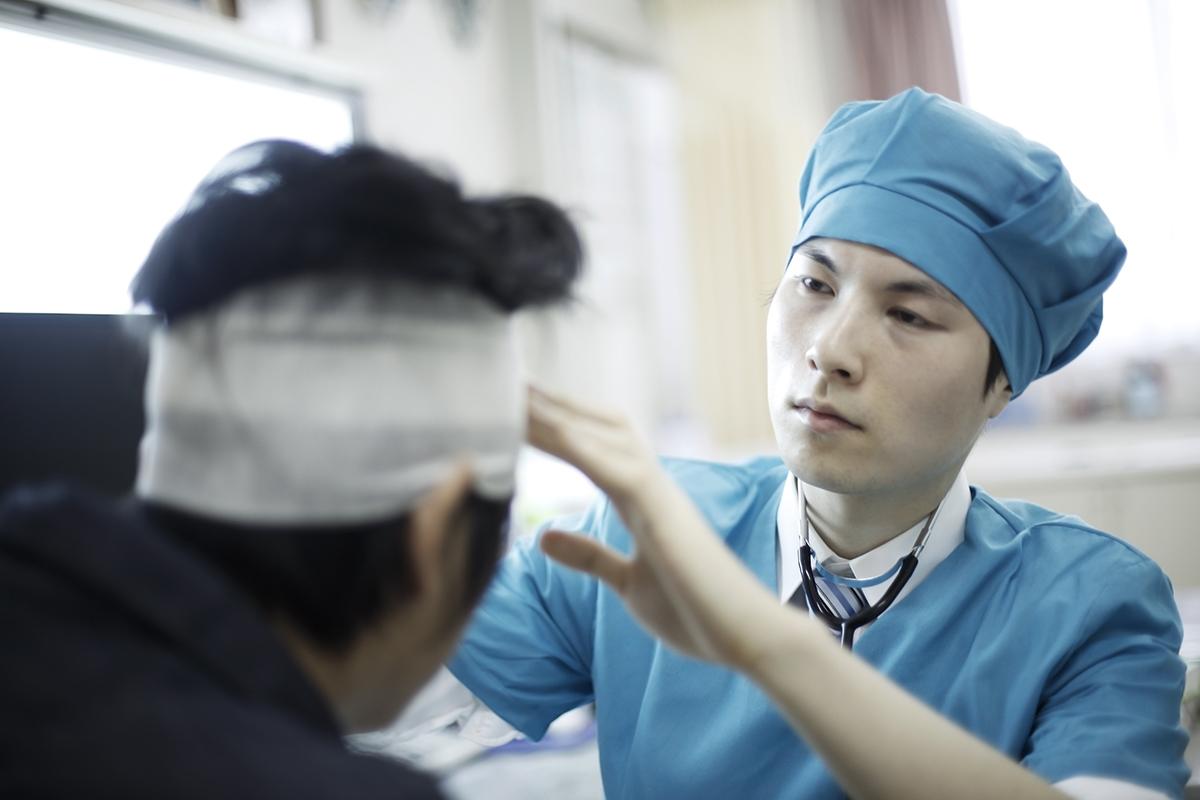 person having their head bandaged