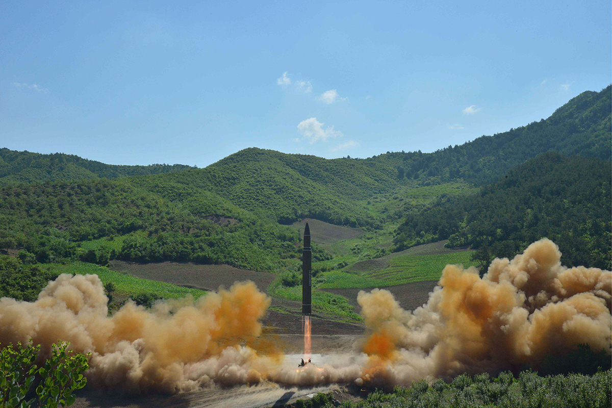 A missile blasts off again the background of green hills