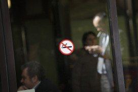 A man behind a no smoking sign