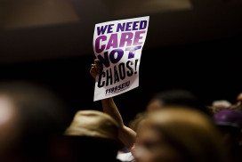 """Person in a crowd holding a sign that says """"We need care not chaos"""""""
