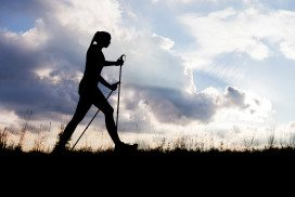 Woman walking againt the skyline with walking poles