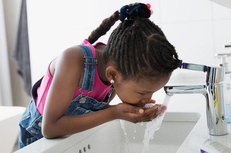 A young girl drinking water from a tap