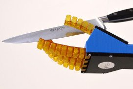 A robotic hand with jelly-like fingers holds a kitchen knife