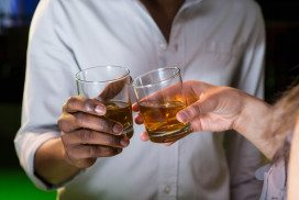 People clinking glasses of whisky