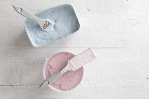 Two open tins of paint side by side on teh floor – one is blue, the other is pink